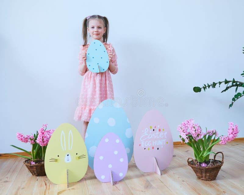 一件礼服的复活节2019美丽的女孩有复活节装饰的 大复活节彩蛋和兔宝宝,五颜六色的地方 很多 库存照片