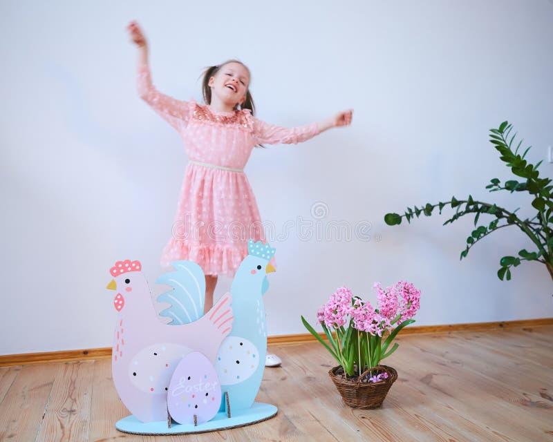 一件礼服的复活节2019美丽的女孩有复活节装饰的 大复活节彩蛋和兔宝宝,五颜六色的地方 很多 免版税库存照片