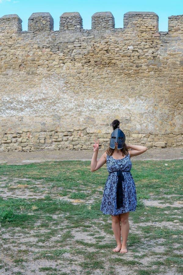 一件礼服的女孩有在她的头的一件盔甲的在堡垒墙壁附近 免版税图库摄影