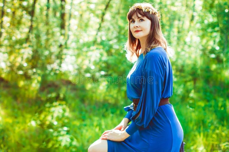 一件礼服的妇女在森林 免版税图库摄影