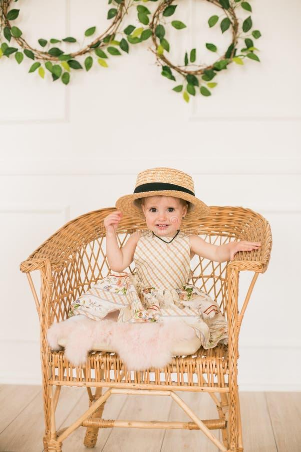 一件礼服的逗人喜爱的女孩有一个花卉图案和草帽的是在复活节风景的一个船民在演播室 免版税库存照片