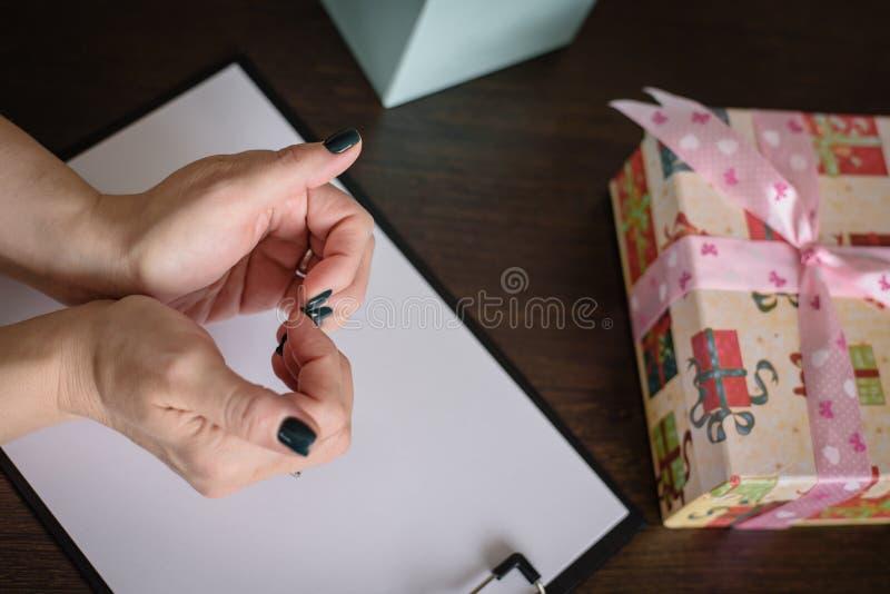 一件礼物的概念为充满爱的假日 妇女的手根据心脏,在桌上的礼物加入了与弓在 免版税图库摄影