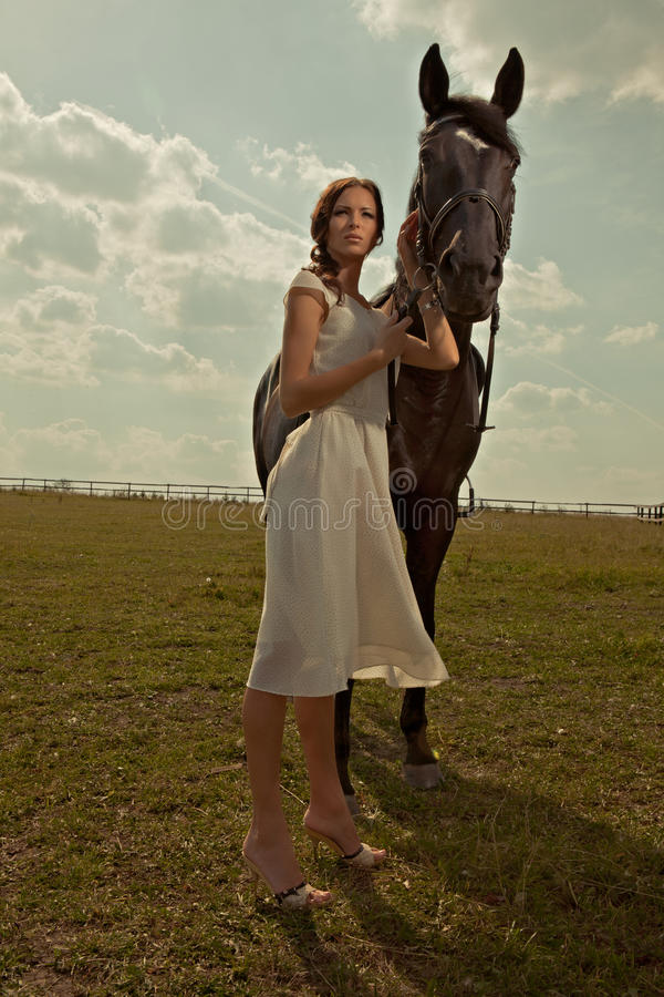 一件空白褂子的美丽的女孩与马 免版税库存图片