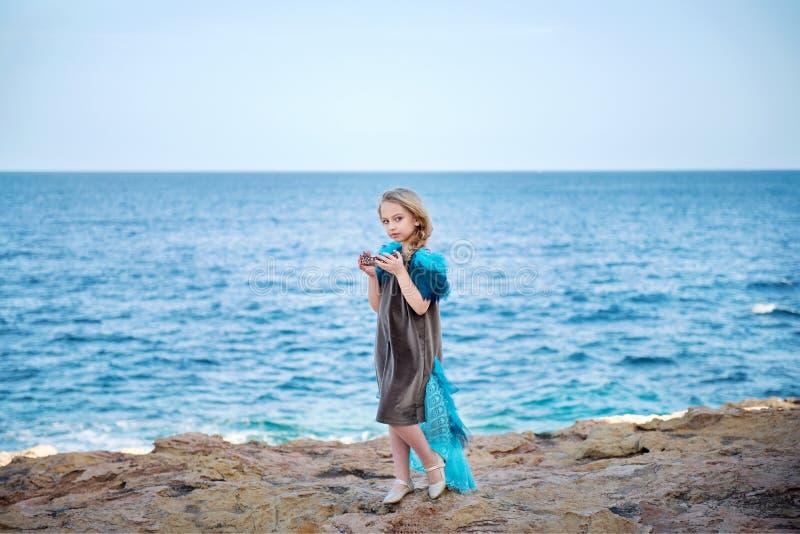 一件童话礼服的年轻白肤金发的女孩象鸟拿着皇家冠漫步沿岸的 免版税库存照片