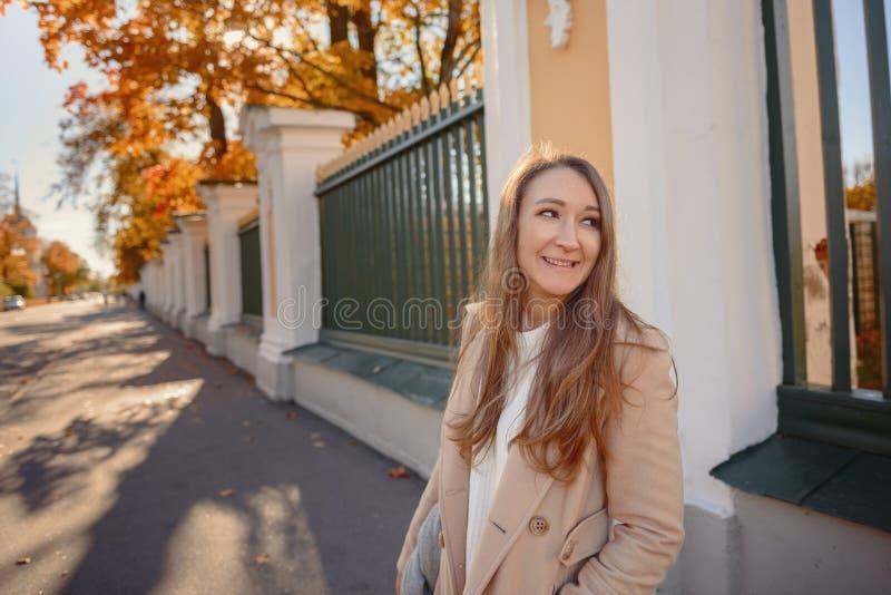 一件米黄外套和一件黑礼服的一个女孩在秋天公园 有长发的一个肉欲的女孩 秋天女孩留下黄色 贴现女孩桃红色购物口气 免版税图库摄影