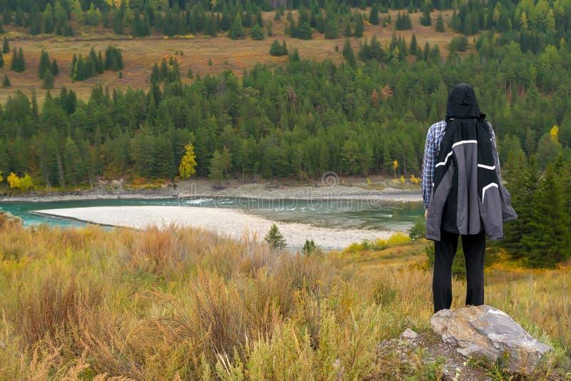一件粗呢夹克的一个人在山看看与森林和绿松石河的秋天风景 免版税图库摄影