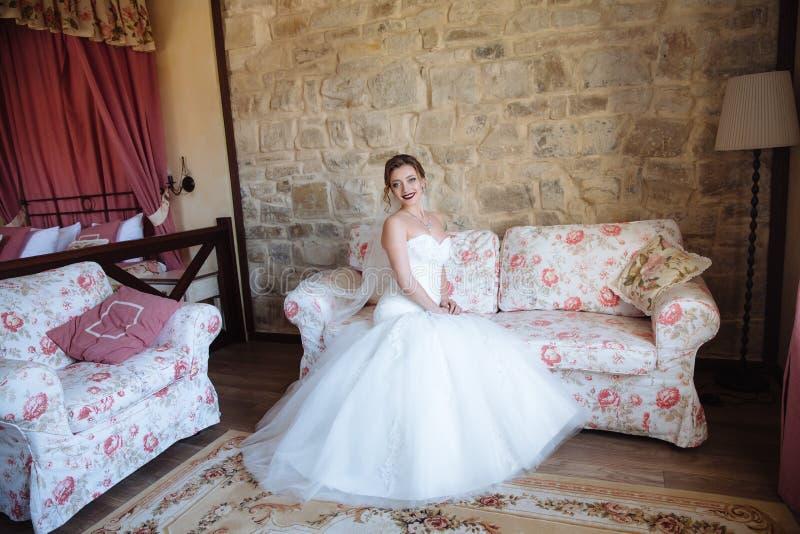 一件紧的白色礼服的一个女孩坐在沙发边缘在她的屋子里 木房子和舒适大气做 免版税库存照片