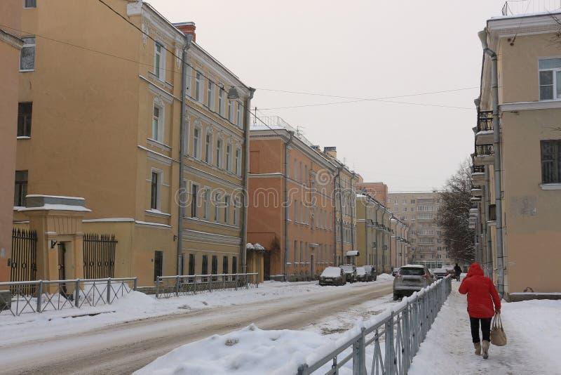 一件红色夹克的一名妇女步行沿着向下城市街道的在飞雪期间 库存图片