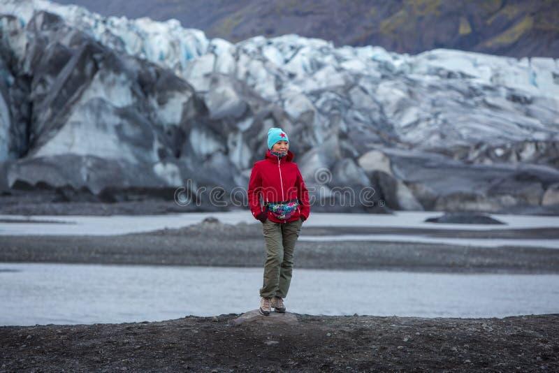 一件红色夹克的女孩在冰川的背景站立 免版税库存图片