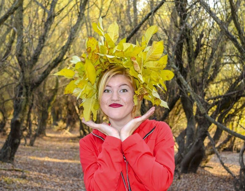 一件红色夹克的女孩有黄色秋叶花圈的  秋天的女王/王后 小姐秋天 秋天结构 免版税图库摄影