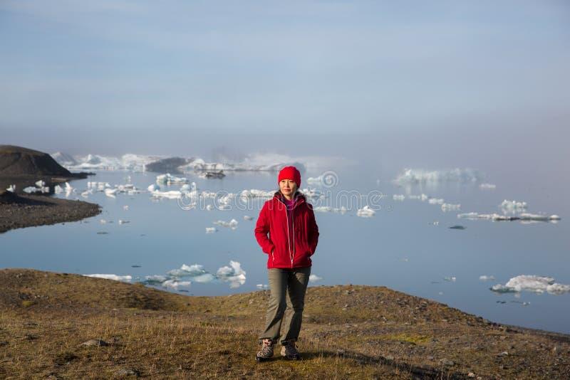 一件红色夹克的女孩站立在日出反对一个glasser盐水湖的背景雾的 免版税库存照片