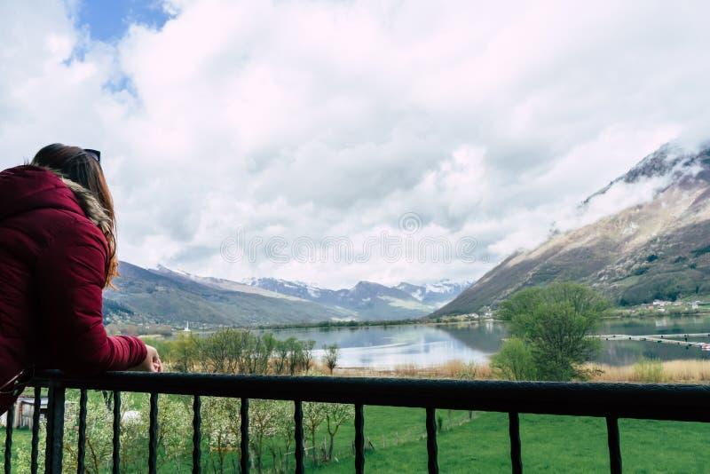 一件红色夹克礼服的美女在山和湖背景的日落  在有多云天空的一个阳台上放松女孩 库存照片