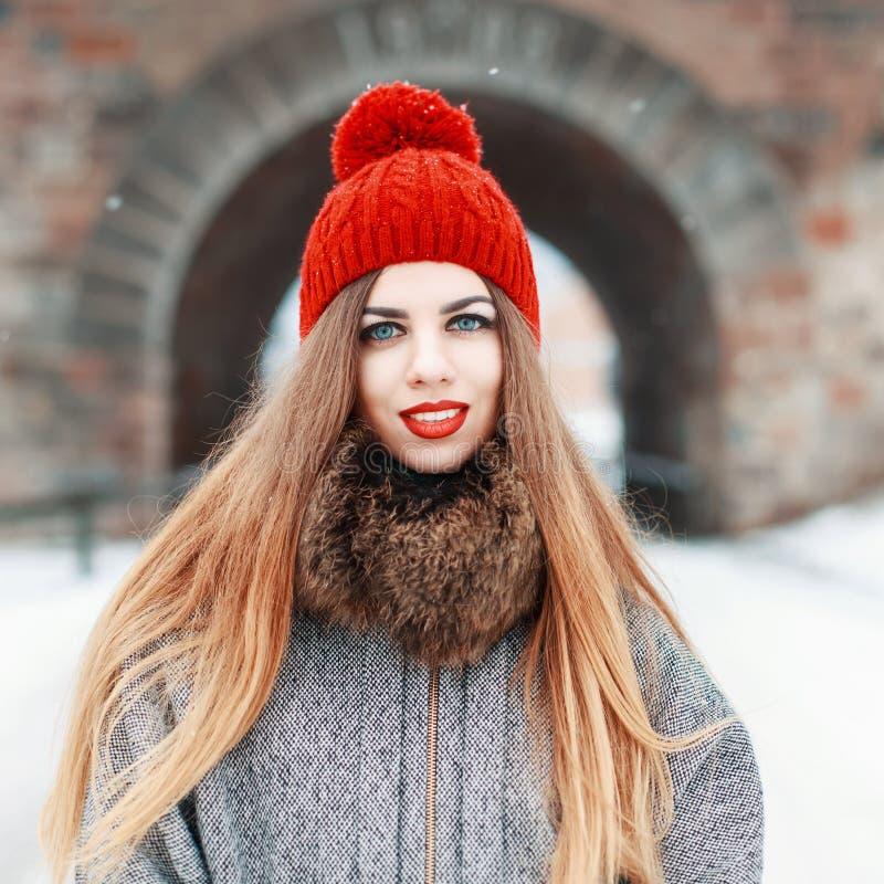 一件红色帽子和外套的年轻美丽的妇女有毛皮的在一个冬天 库存照片