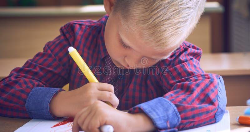 一件红色方格的衬衣的逗人喜爱的小男孩和画与在学校笔记本的一支毡尖的笔 免版税图库摄影