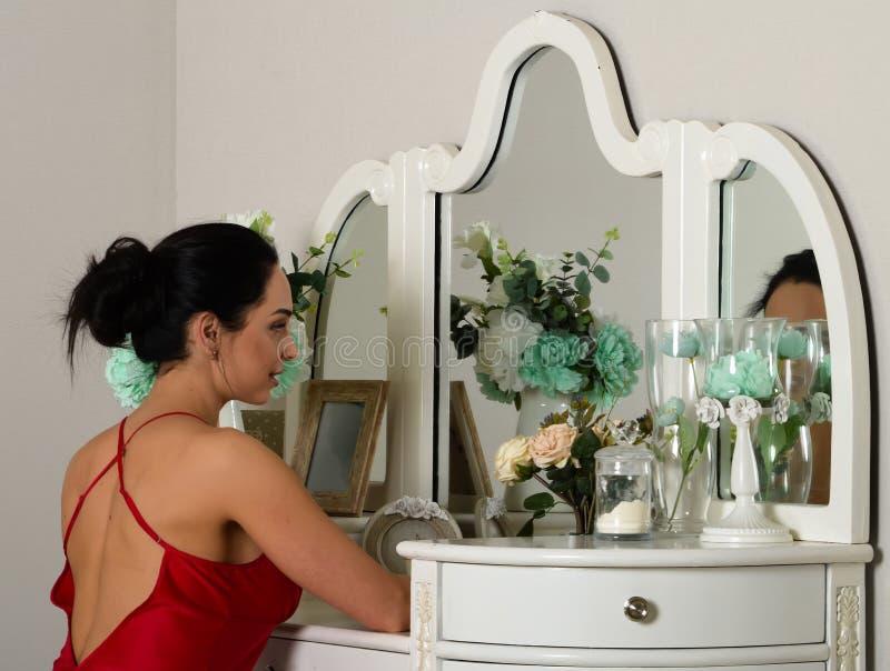 一件红色晨衣的一个美丽的女孩 免版税库存图片