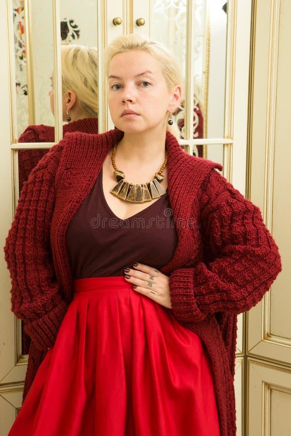 一件红色毛线衣、伯根地裙子和种族装饰品的年轻金发碧眼的女人在镜子旁边 图库摄影