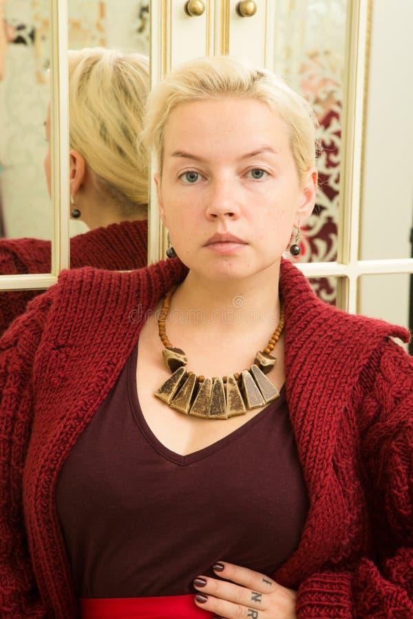 一件红色毛线衣、伯根地裙子和种族装饰品的年轻金发碧眼的女人在镜子旁边 库存照片