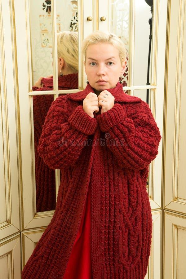 一件红色毛线衣、伯根地裙子和种族装饰品的年轻金发碧眼的女人在镜子旁边 免版税库存照片