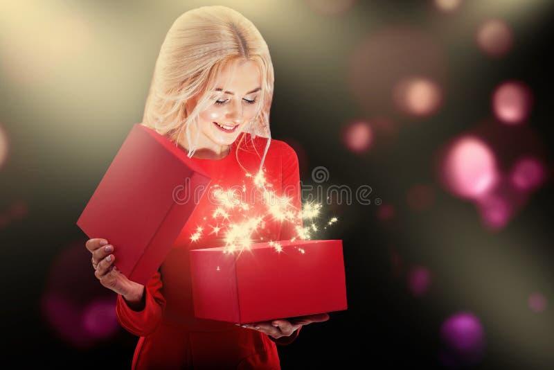 一件红色礼服的一个年轻金发碧眼的女人撕毁礼物盒 从箱子有明亮的光和星 库存照片