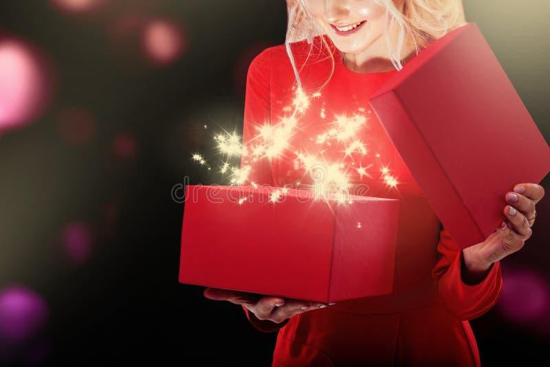 一件红色礼服的一个年轻金发碧眼的女人撕毁礼物盒 从箱子有明亮的光和星 库存图片