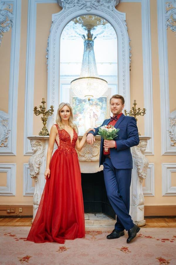 一件红色礼服的一美女站立与人、新娘和新郎,愉快的新婚佳偶 免版税图库摄影