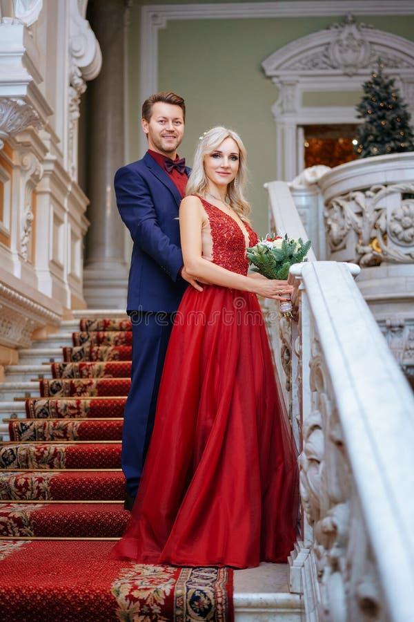 一件红色礼服的一美女站立与人、新娘和新郎,愉快的新婚佳偶 免版税库存图片