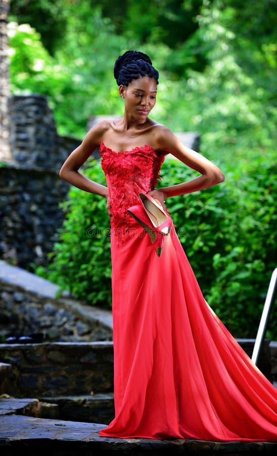 一件红色礼服的非裔美国人的女孩,有dreadlocks的,与在手中红色鞋子,摆在夏天在公园 免版税库存图片