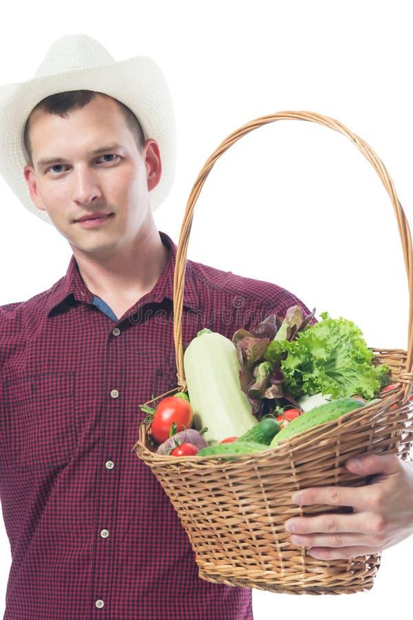一件红色衬衣的农夫有菜篮子的  库存照片