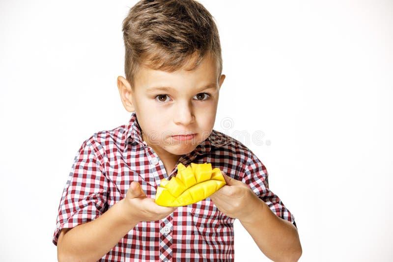 一件红色衬衣的帅哥吃着一个芒果 免版税图库摄影