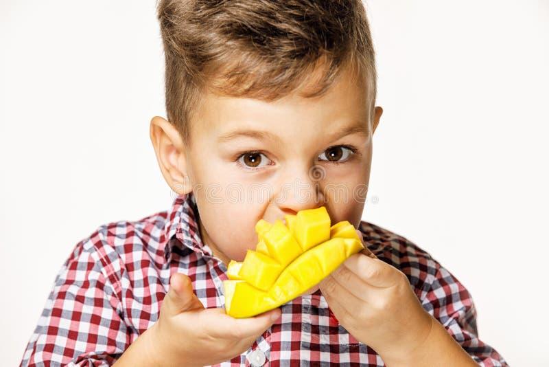 一件红色衬衣的帅哥吃着一个芒果 库存图片
