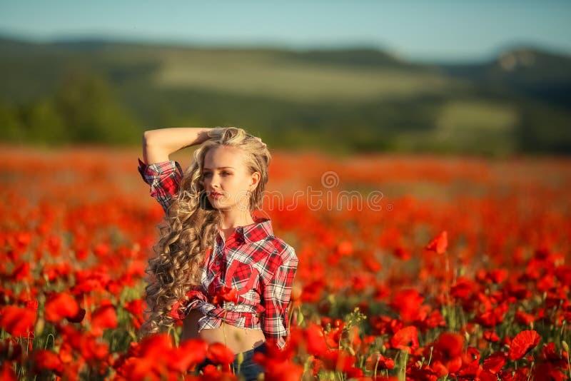 一件红色衬衣的年轻金发碧眼的女人在鸦片花田 免版税库存图片