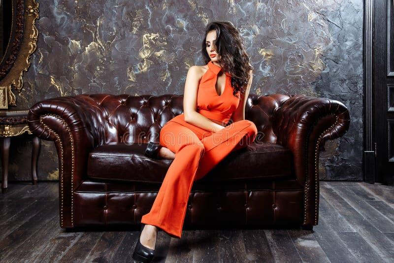 一件红色长裤套装的端庄的妇女坐长沙发 免版税库存图片