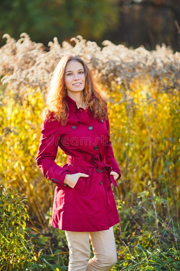 一件红色雨衣的美丽的年轻微笑的妇女 图库摄影