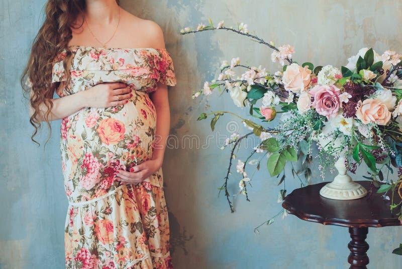 一件美丽的五颜六色的礼服的孕妇在花旁边明亮的花束站立并且在家握在腹部inte的手 免版税库存图片