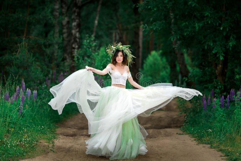 一件美丽的白色礼服和森林流程花圈的新娘  免版税库存图片