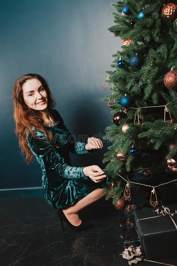 一件美丽的礼服的华美的妇女在与礼物盒的圣诞树旁边,微笑 新年和圣诞装饰概念 免版税库存照片