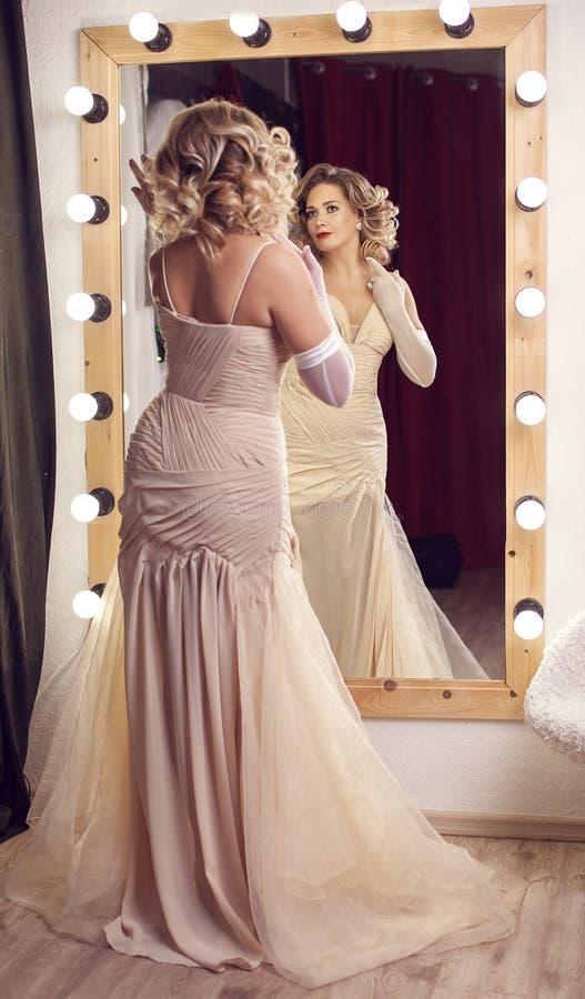 一件美丽的礼服的女孩在镜子旁边 免版税图库摄影