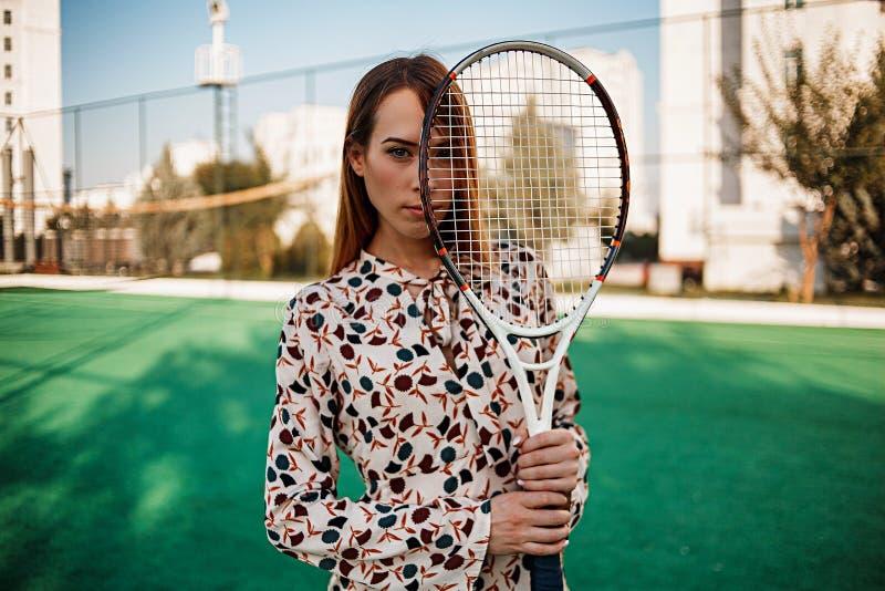 一件美丽的礼服的女孩有一副球拍的在她的手上在网球场 库存图片