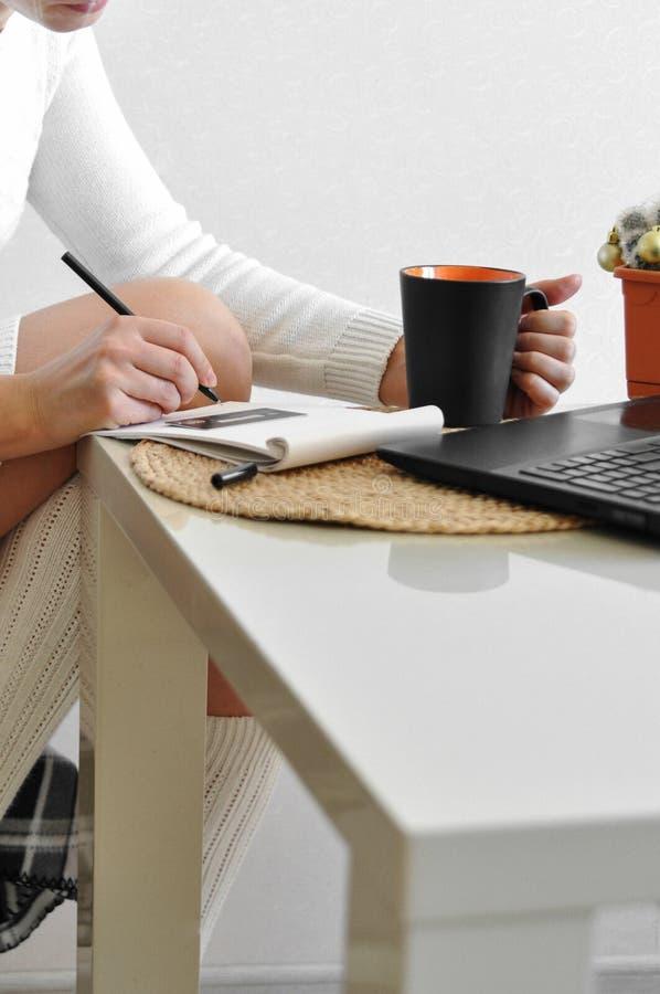 一件舒适白色毛线衣和袜子的一个主妇女孩在与毯子的一把椅子与一台膝上型计算机一起使用在厨房里 网上购物的w 免版税库存图片