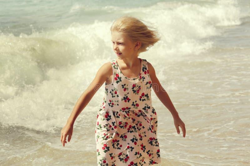 一件色的礼服的愉快和美丽的白肤金发的女孩走在海滩和看波浪的 E 免版税图库摄影