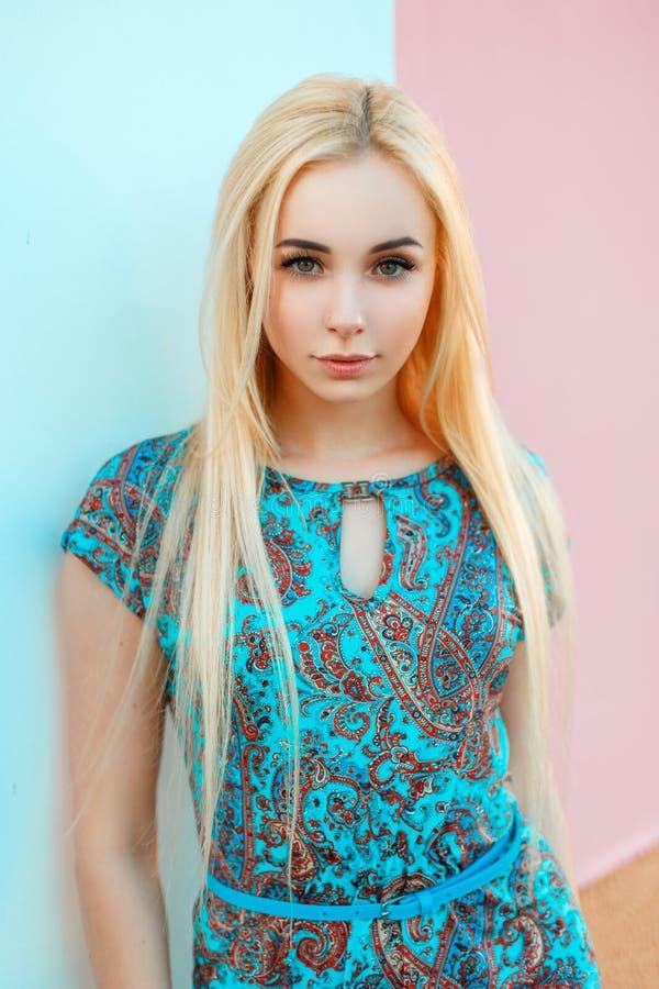 一件蓝色夏天礼服的美丽的年轻白肤金发的妇女 库存图片