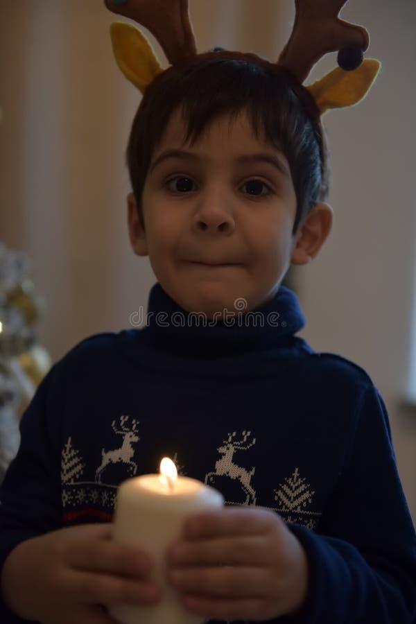 一件蓝色毛线衣的男孩在与鹿垫铁的圣诞树和一个蜡烛在他的手上 图库摄影