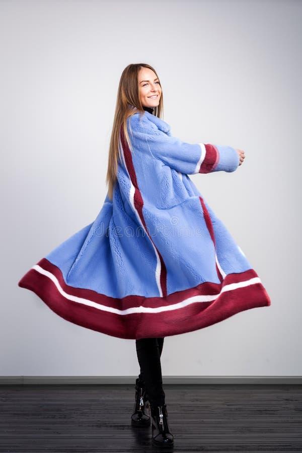 一件蓝色皮大衣的深色头发的妇女 免版税库存照片