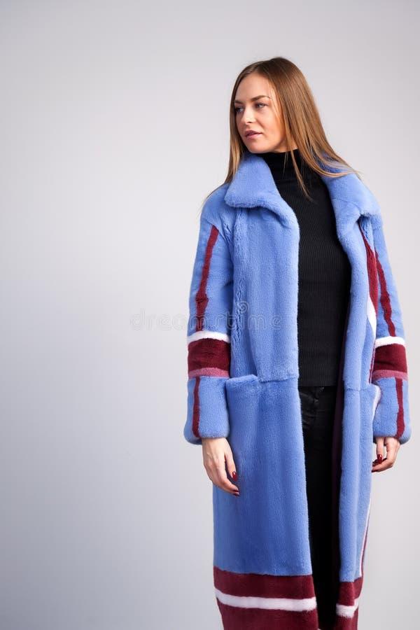 一件蓝色皮大衣的深色头发的妇女 免版税库存图片