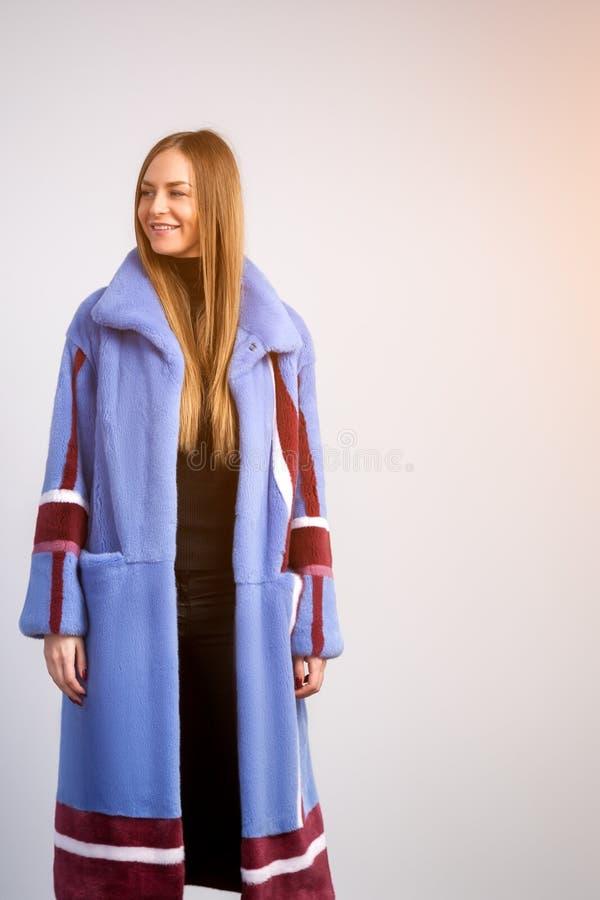 一件蓝色皮大衣的深色头发的妇女 库存图片