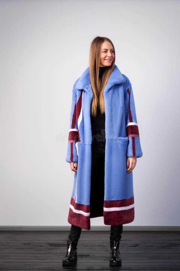 一件蓝色皮大衣的深色头发的妇女 库存照片