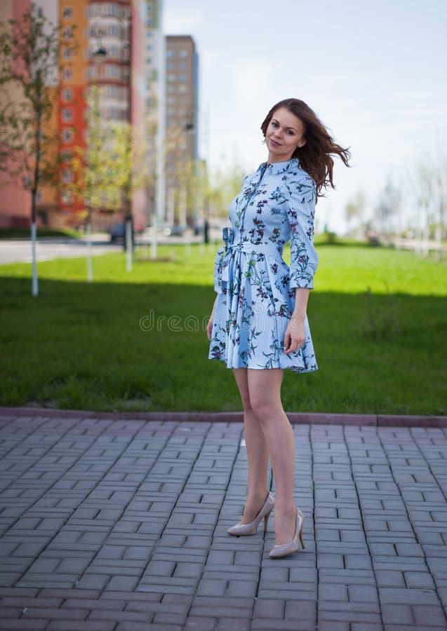 一件蓝色短的礼服的美丽的女孩花费以街道为背景每个有风晴天 库存图片