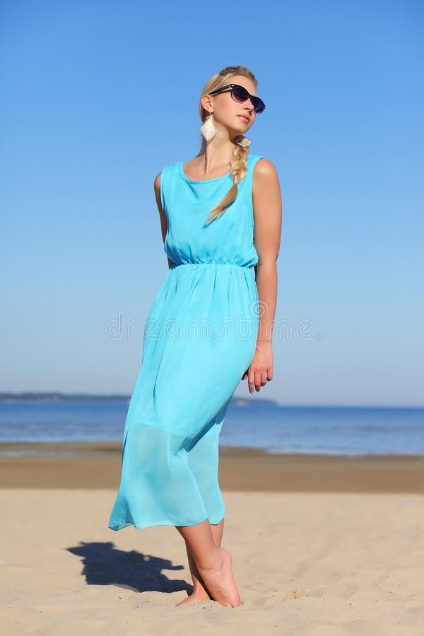一件蓝色礼服和太阳镜的少女在天空背景  图库摄影