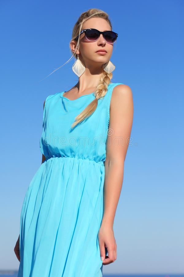 一件蓝色礼服和太阳镜的少女在天空背景  免版税库存照片