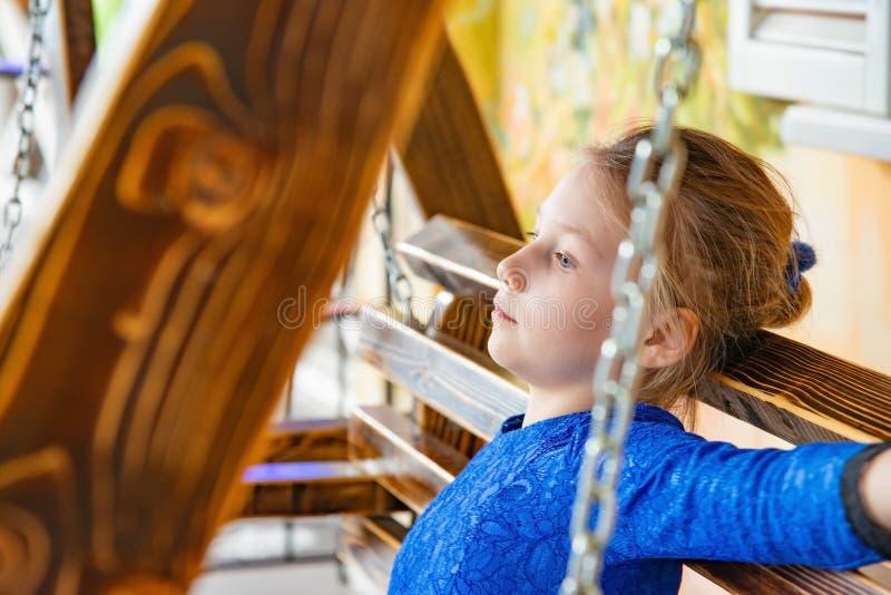 一件蓝色礼服的一个女孩坐摇摆,考虑她的将来人生 图库摄影